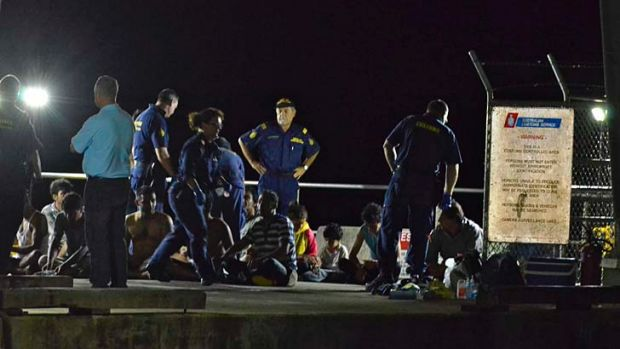 Customs officers and rescue personnel watch over survivors of the vessel that capsized on Tuesday.