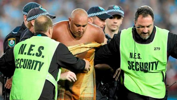 Sent off: a streaker is escorted from the field.
