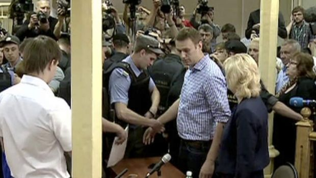 A police officer puts on handcuffs on Russian opposition leader Alexei Navalny after a trial in Kirov, Russia, Thursday, ...