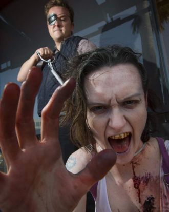 Cosplayers husband and wife duo, John Randolph (L) and Vylet Randolph, are dressed as the Governor and a zombie from ...