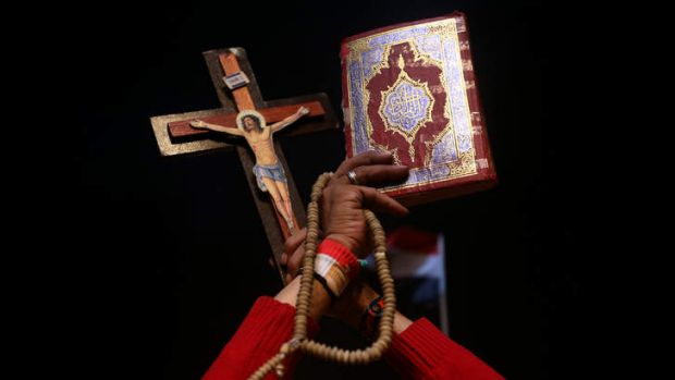 An opponent of ousted President Mohammed Mursi holds up Islam's holy book Koran, right, and Christian cross to show ...