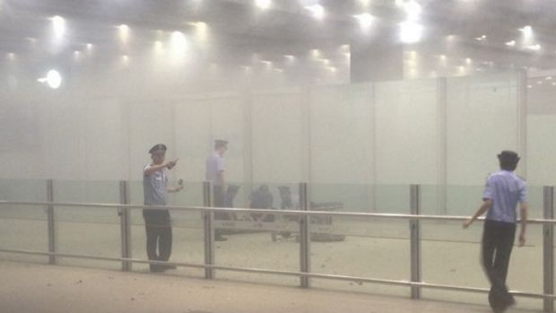 A mobile phone photo of police officers work at terminal 3 after the homemade bomb exploded at Beijing's international ...