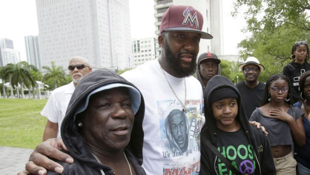 Tracy Martin, centre, father of Trayvon Martin, poses for photos with supporters wearing hoodies at a 'Justice for ...