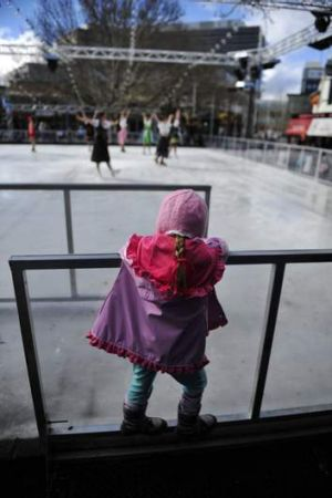 A young member of the crowd watches the ACT Ice Skaters perform at the ice skating rink at Civic on Saturday.