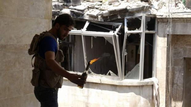 A Free Syrian Army fighter carries a Molotov cocktail to be thrown at forces loyal to Syria's President Bashar al-Assad ...