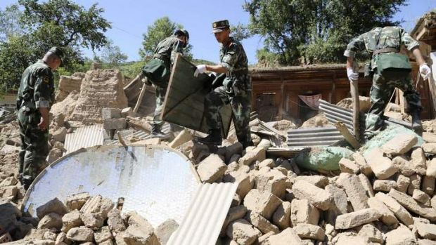 Toll rises: Paramilitary policemen search for victims amid collapsed houses.