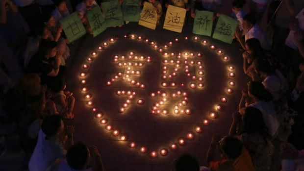 """Residents light candles that form the words """"Dingxi July 22"""" while holding up the characters """"Gansu, Dingxi, Go on! Best ..."""
