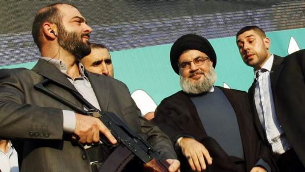 Lebanon's Hezbollah leader Sayyed Hassan Nasrallah (2nd R), escorted by his bodyguards, greets his supporters at an ...
