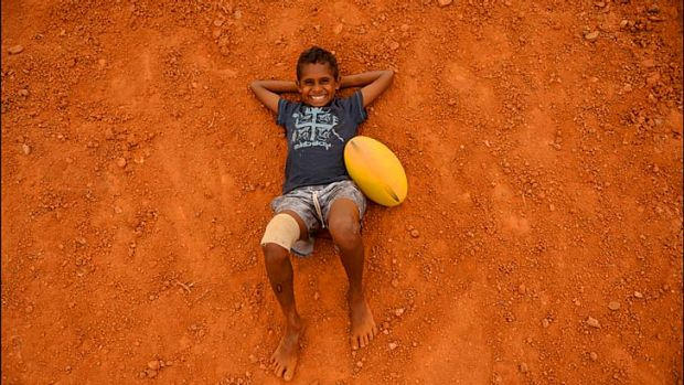 At the Gunbalanya School in Arnhem Land, Junior Dirdi relaxes after a long afternoon kicking the footy.