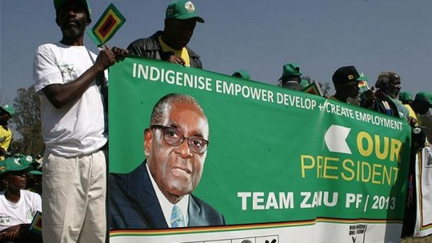 Zanu-PF activists hold a banner featuring the 33-year-old picture of Robert Mugabe