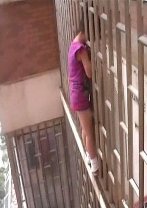 Girl climbed outside the building and got her head stuck between the metal window bars.