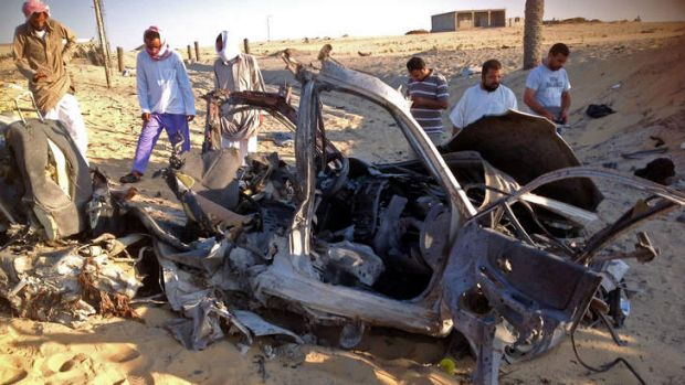 Egyptians gather near a damaged car bomb that detonated before reaching the intended target killing three passengers in ...