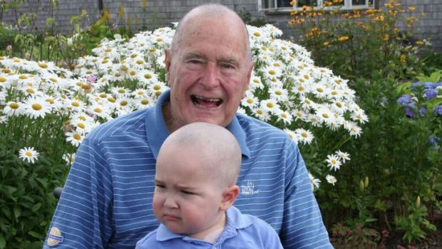 Former US President George H. W. Bush poses with his head shaved to show support for two year-old Patrick, the son of a ...