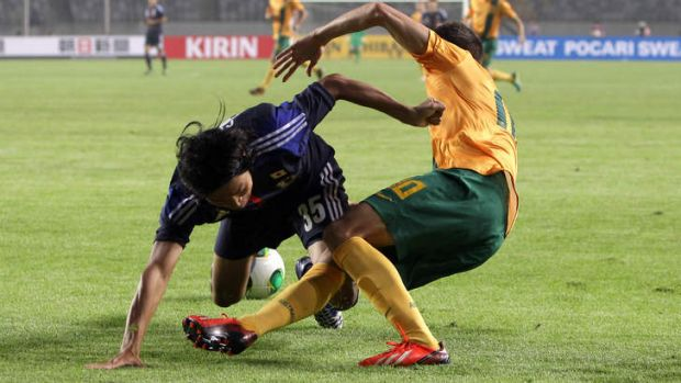 Dario Vidosic of Australia and Kazuhiko Chiba of Japan fall over each other in contest for the ball.