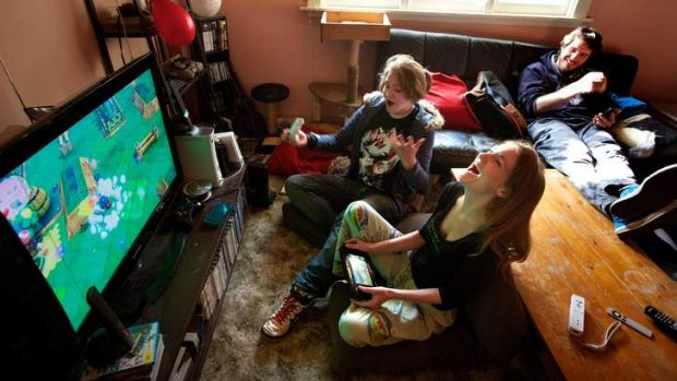 Gender balance: Kyah Horrocks plays a video game with sister Sian while friends look on.
