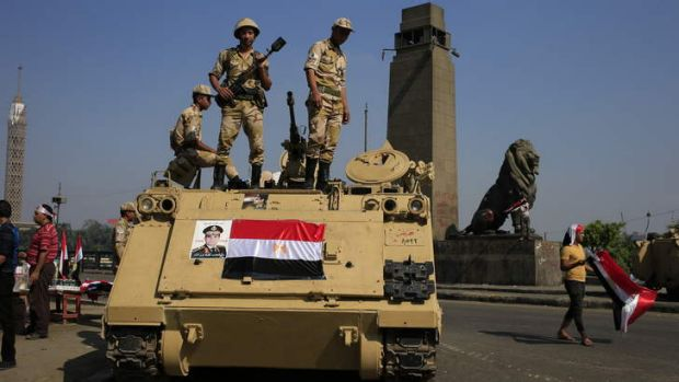 Lockdown: Egyptian soldiers stand guard atop an armoured personnel vehicle on a bridge that leads to Tahrir Square in Cairo.