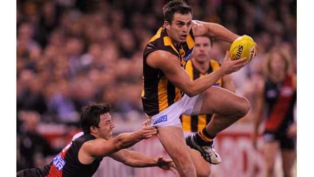 Essendon's Michael Hibberd makes a grab for Hawthorn's Brian Lake.