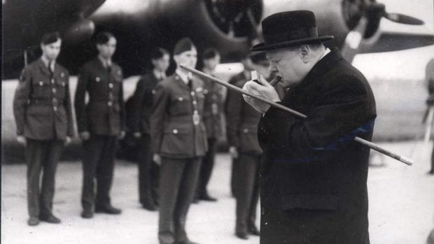 Winston Churchill lights a cigar before inspecting English and American bombers at an RAF station.