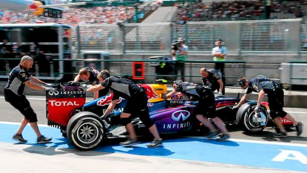 Mechanics push the car of Red Bull Racing's Australian driver Mark Webber into the pits during the third practice ...