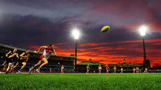 Red flash: As the setting sun leaves its dazzling mark, Sydney's Josh Kennedy leads the race for the ball at the SCG on ...