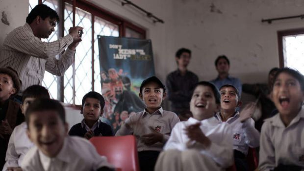 Pakistani orphans reacts while watching an early screening of the first episode of the animates Burka Avenger series, at ...