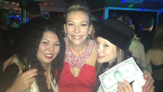 """Mrs Gaskin with party guests and printed """"Georgie dollars""""."""