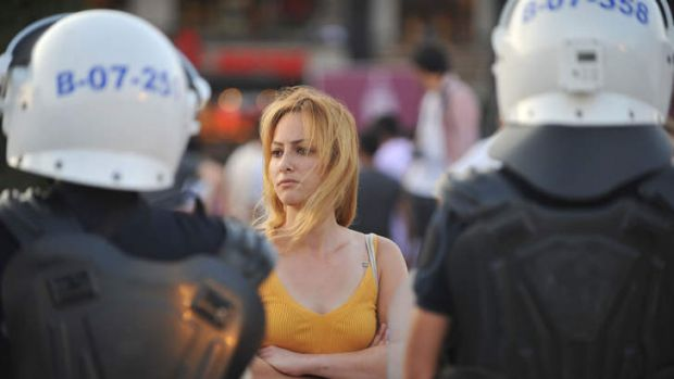 An anti-goverment protestor is surrounded by Turkish riot police during a demonstration in an Istanbul park.