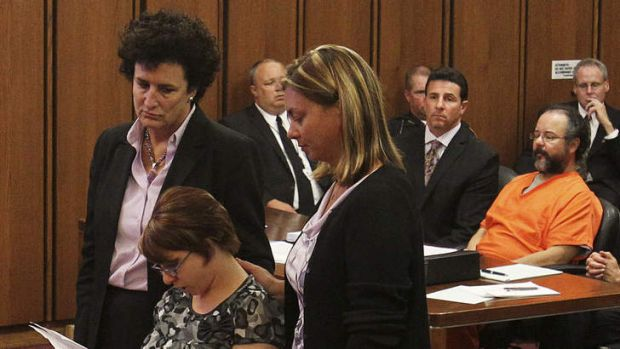 Michelle Knight reads statements while supported by her attorney and friend as her accused assailant Ariel Castro sits ...