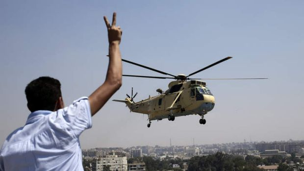 Strong presence: A man flashes a victory sign at an Egyptian military helicopter as it flies over the presidential ...