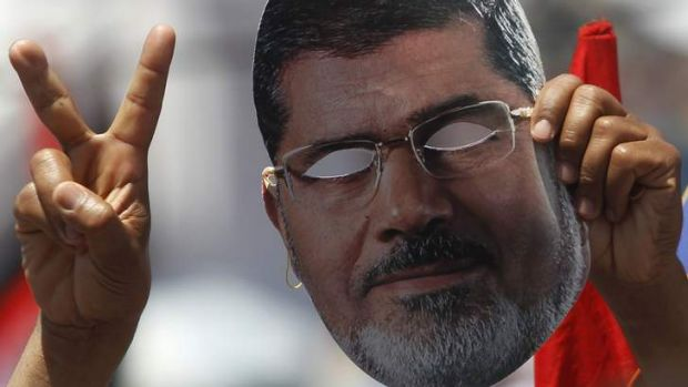Unmasked: A supporter of ousted Egyptian president Mohamed Mursi holds up a mask at a rally in Cairo.