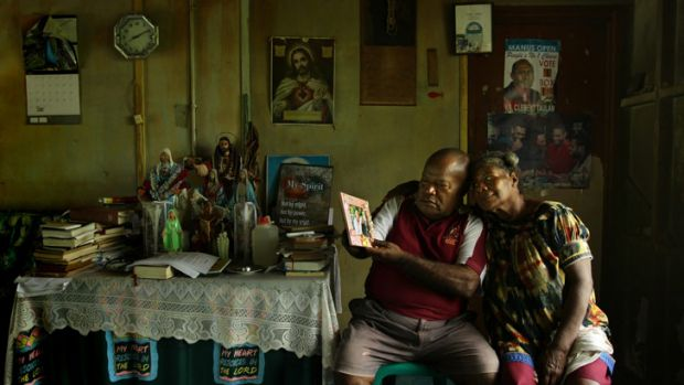 Grieving: James Sipuan and his wife, Caroline, look at a photo of  son Raymond who died after allegedly being bashed by ...