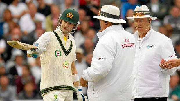 Michael Clarke with umpires Tony Hill (R) and Marais Erasmus after play is stopped for bad light.