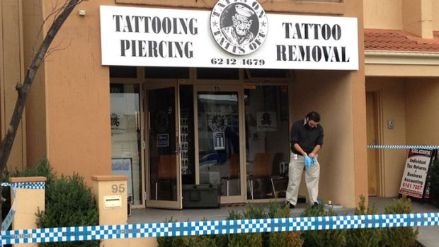 UNDER FIRE: An investigator at the Tatts On Tatts Off tattoo parlour where bullet holes were discovered in the shop ...