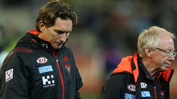 Bombers coach James Hird walks off the MCG with Dr Bruce Reid (R) on Sunday.