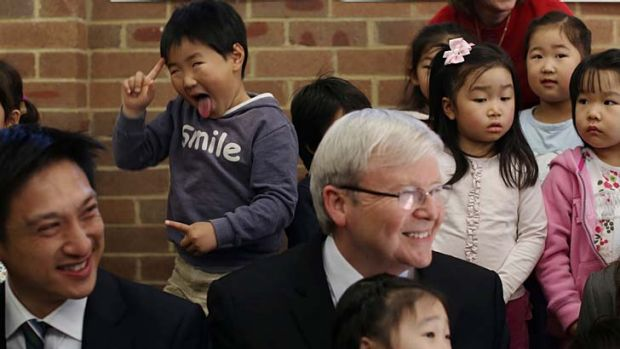 Photobomb: Joseph Kim poses behind Prime Minister Kevin Rudd at the Ryde Uniting Church in Sydney.
