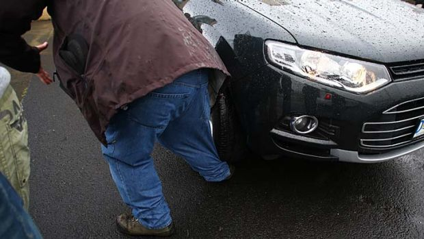 Freelance photographer John Voss's foot is run over by Prime Minister Kevin Rudd's protection team vehicle as they ...