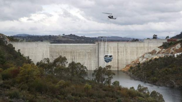 A helicopter lifts a ResMix system into position at Cotter Dam.