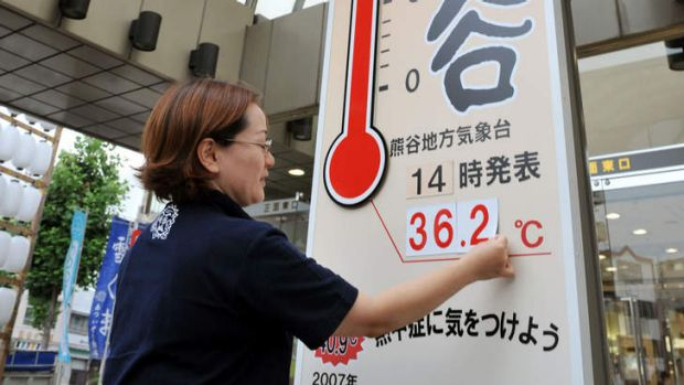 Hot days: A worker at a department store puts up the current temperature in Kumagaya, Saitama prefecture, on Sunday.