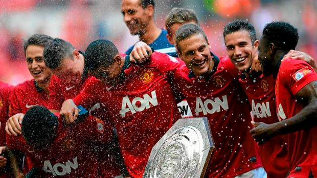 (From right) Danny Welbeck, Robin van Persie and Nemanja Vidic of Manchester United celebrate with the trophy.