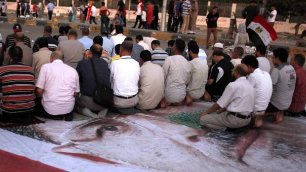 Members of the Muslim Brotherhood and supporters of deposed Egyptian President Mohamed Mursi pray on a giant poster, ...
