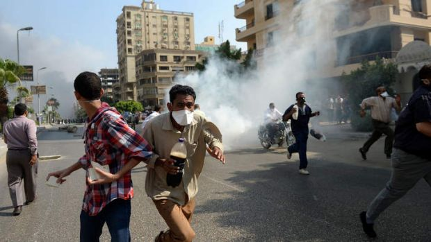 Egyptian Muslim Brotherhood supporters run from tear gas fired by Egyptian police.
