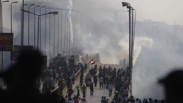 Members of the Muslim Brotherhood and supporters of ousted Egyptian President Mohamed Mursi flee from tear gas and ...