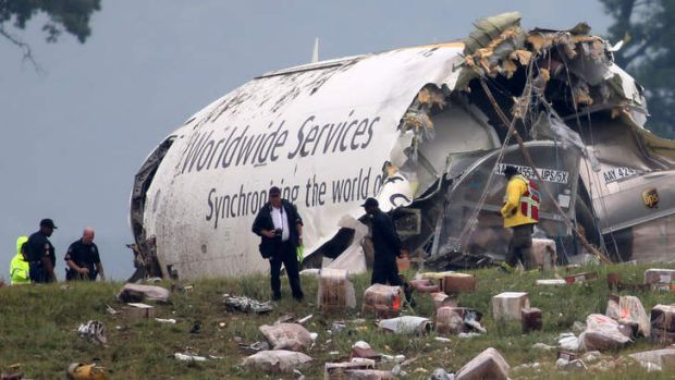 Investigators look through debris of a UPS A300 cargo plane after it crashed on approach to Birmingham, Alabama.