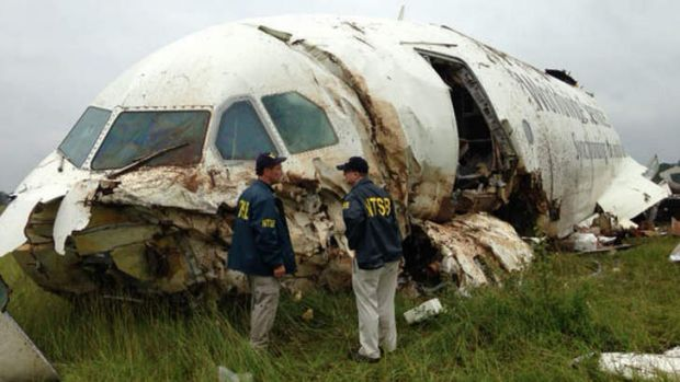 The National Transportation Safety Board shows investigators near the remains of a UPS cargo plane that crashed ...