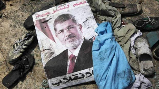 """A poster of deposed Egyptian President Mohamed Mursi that reads """"No to the coup"""" lies amid the debris of a cleared ..."""