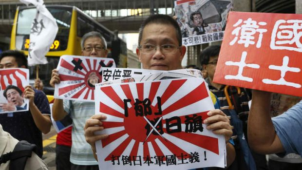 "Anti-Japan protesters demonstrate with Japanese military flags with Chinese words, "" Down with Japan militarism ""  in ..."