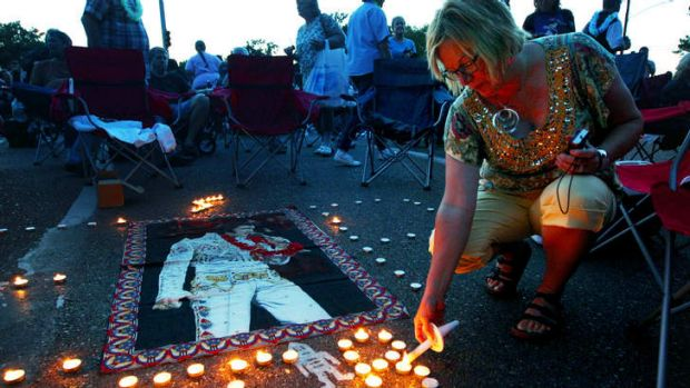 Elvis Presley fan Jill Gibson lights candles outside Graceland, Presley's home, before the annual candlelight vigil in ...