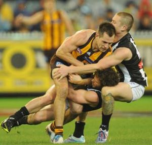 Hard man to keep in check: Hawthorn's Luke Hodge is brought to a halt, but it took the efforts of Jarryd Blair and Dayne ...