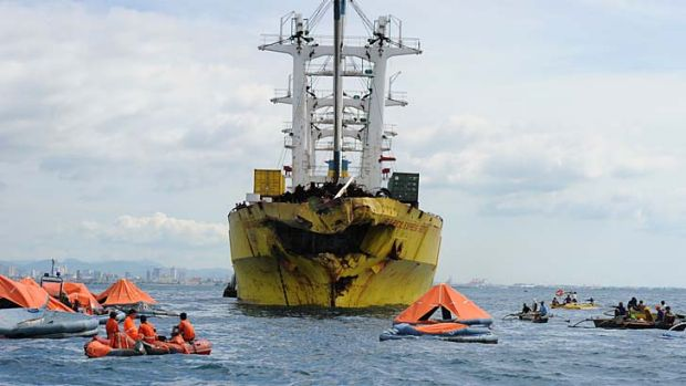 Hundreds missing: Life rafts from the sunken ferry St. Thomas Aquinas float in front of a cargo ship on whose bow was ...