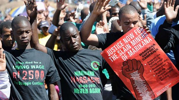 Co-workers of 34 miners shot dead by South African police during a violent wage strike pray during a ceremony to mark ...